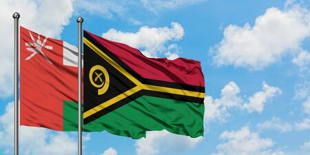 Oman and Vanuatu flag waving in the wind against white cloudy blue sky together. Diplomacy concept, international relations.
