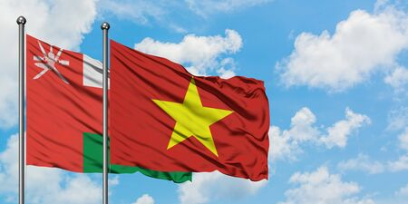 Oman and Vietnam flag waving in the wind against white cloudy blue sky together. Diplomacy concept, international relations.
