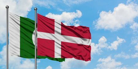 Pakistan and Denmark flag waving in the wind against white cloudy blue sky together. Diplomacy concept, international relations.
