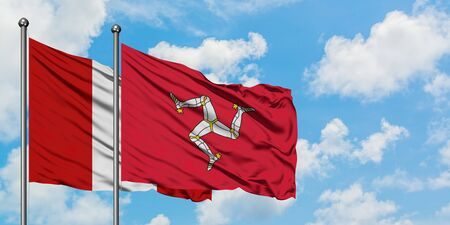Peru and Isle Of Man flag waving in the wind against white cloudy blue sky together. Diplomacy concept, international relations. Banque d'images