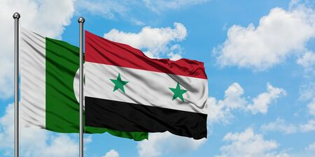 Pakistan and Syria flag waving in the wind against white cloudy blue sky together. Diplomacy concept, international relations.