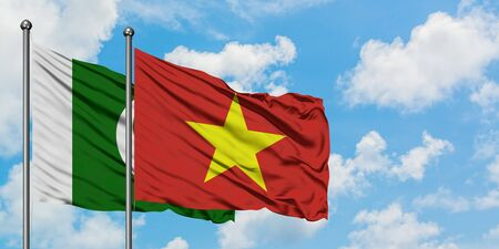 Pakistan and Vietnam flag waving in the wind against white cloudy blue sky together. Diplomacy concept, international relations.