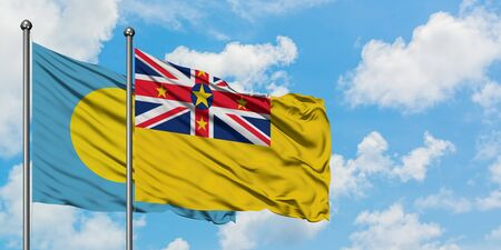 Palau and Niue flag waving in the wind against white cloudy blue sky together. Diplomacy concept, international relations.