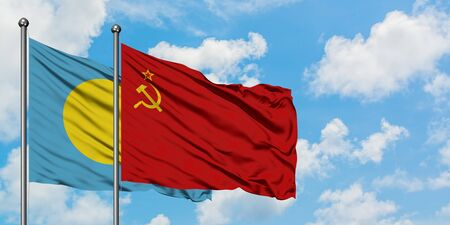 Palau and Soviet Union flag waving in the wind against white cloudy blue sky together. Diplomacy concept, international relations.