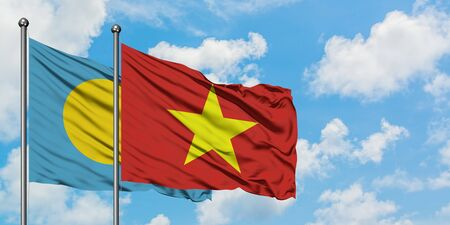 Palau and Vietnam flag waving in the wind against white cloudy blue sky together. Diplomacy concept, international relations.