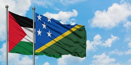 Palestine and Solomon Islands flag waving in the wind against white cloudy blue sky together. Diplomacy concept, international relations.