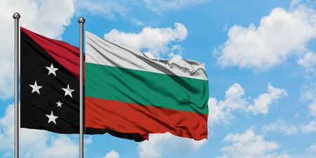Papua New Guinea and Bulgaria flag waving in the wind against white cloudy blue sky together. Diplomacy concept, international relations.