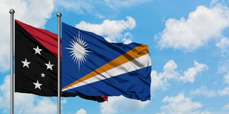 Papua New Guinea and Marshall Islands flag waving in the wind against white cloudy blue sky together. Diplomacy concept, international relations.