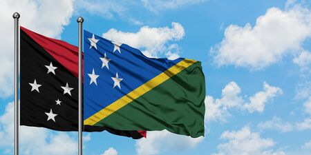 Papua New Guinea and Solomon Islands flag waving in the wind against white cloudy blue sky together. Diplomacy concept, international relations.