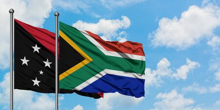Papua New Guinea and South Africa flag waving in the wind against white cloudy blue sky together. Diplomacy concept, international relations.