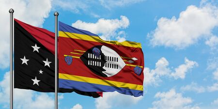 Papua New Guinea and Swaziland flag waving in the wind against white cloudy blue sky together. Diplomacy concept, international relations.