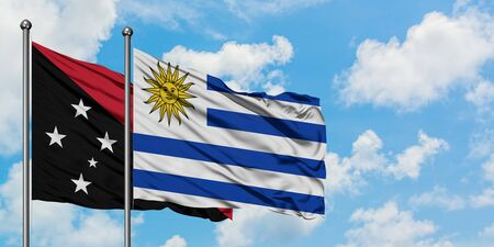 Papua New Guinea and Uruguay flag waving in the wind against white cloudy blue sky together. Diplomacy concept, international relations.