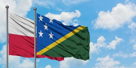 Poland and Solomon Islands flag waving in the wind against white cloudy blue sky together. Diplomacy concept, international relations.
