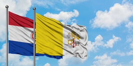 Paraguay and Vatican City flag waving in the wind against white cloudy blue sky together. Diplomacy concept, international relations.