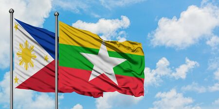 Philippines and Myanmar flag waving in the wind against white cloudy blue sky together. Diplomacy concept, international relations.