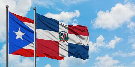 Puerto Rico and Dominican Republic flag waving in the wind against white cloudy blue sky together. Diplomacy concept, international relations.
