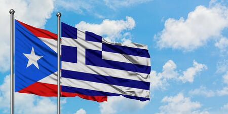 Puerto Rico and Greece flag waving in the wind against white cloudy blue sky together. Diplomacy concept, international relations.