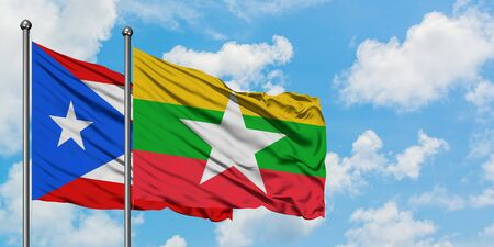 Puerto Rico and Myanmar flag waving in the wind against white cloudy blue sky together. Diplomacy concept, international relations. Stok Fotoğraf