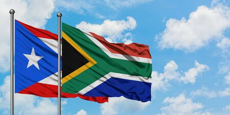 Puerto Rico and South Africa flag waving in the wind against white cloudy blue sky together. Diplomacy concept, international relations.