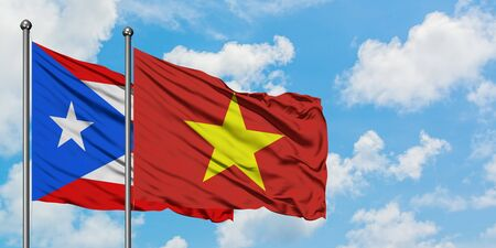 Puerto Rico and Vietnam flag waving in the wind against white cloudy blue sky together. Diplomacy concept, international relations. Stock Photo