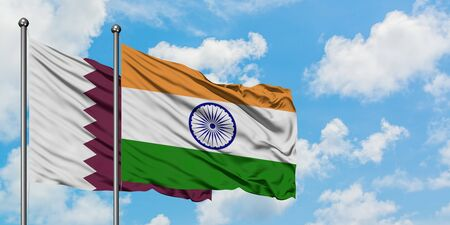 Qatar and India flag waving in the wind against white cloudy blue sky together. Diplomacy concept, international relations.