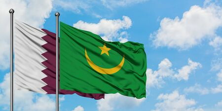 Qatar and Mauritania flag waving in the wind against white cloudy blue sky together. Diplomacy concept, international relations.