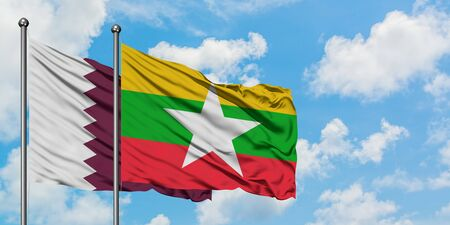 Qatar and Myanmar flag waving in the wind against white cloudy blue sky together. Diplomacy concept, international relations.