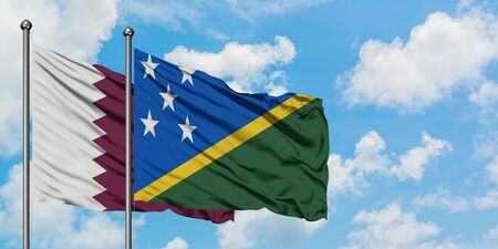 Qatar and Solomon Islands flag waving in the wind against white cloudy blue sky together. Diplomacy concept, international relations.