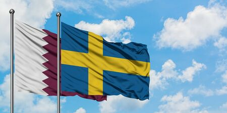 Qatar and Sweden flag waving in the wind against white cloudy blue sky together. Diplomacy concept, international relations.