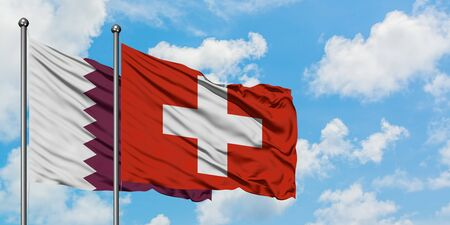 Qatar and Switzerland flag waving in the wind against white cloudy blue sky together. Diplomacy concept, international relations.