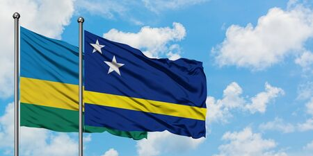 Rwanda and Curacao flag waving in the wind against white cloudy blue sky together. Diplomacy concept, international relations.
