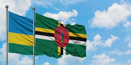 Rwanda and Dominica flag waving in the wind against white cloudy blue sky together. Diplomacy concept, international relations.