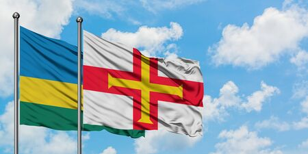 Rwanda and Guernsey flag waving in the wind against white cloudy blue sky together. Diplomacy concept, international relations.