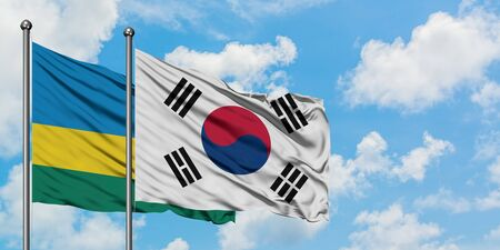 Rwanda and South Korea flag waving in the wind against white cloudy blue sky together. Diplomacy concept, international relations.