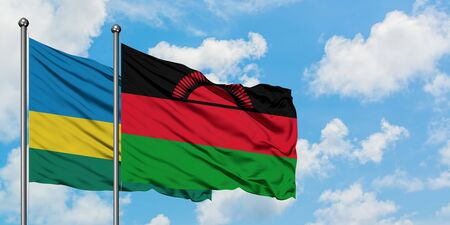 Rwanda and Malawi flag waving in the wind against white cloudy blue sky together. Diplomacy concept, international relations.