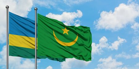 Rwanda and Mauritania flag waving in the wind against white cloudy blue sky together. Diplomacy concept, international relations. Фото со стока
