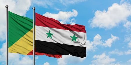 Republic Of The Congo and Syria flag waving in the wind against white cloudy blue sky together. Diplomacy concept, international relations. Banco de Imagens