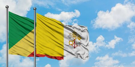 Republic Of The Congo and Vatican City flag waving in the wind against white cloudy blue sky together. Diplomacy concept, international relations.
