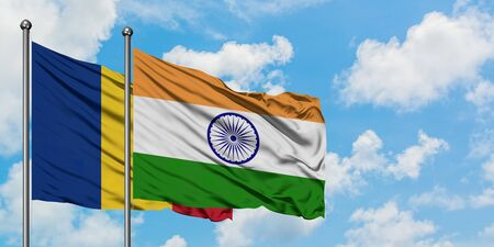 Romania and India flag waving in the wind against white cloudy blue sky together. Diplomacy concept, international relations.