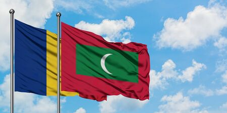 Romania and Maldives flag waving in the wind against white cloudy blue sky together. Diplomacy concept, international relations. Stock Photo