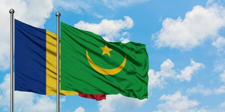 Romania and Mauritania flag waving in the wind against white cloudy blue sky together. Diplomacy concept, international relations.