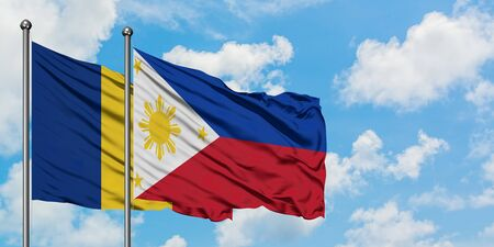 Romania and Philippines flag waving in the wind against white cloudy blue sky together. Diplomacy concept, international relations. Stock Photo