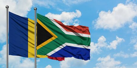 Romania and South Africa flag waving in the wind against white cloudy blue sky together. Diplomacy concept, international relations. Stock Photo