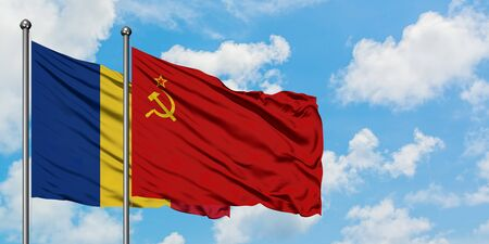 Romania and Soviet Union flag waving in the wind against white cloudy blue sky together. Diplomacy concept, international relations.