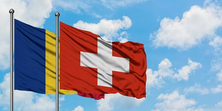 Romania and Switzerland flag waving in the wind against white cloudy blue sky together. Diplomacy concept, international relations. Stock Photo