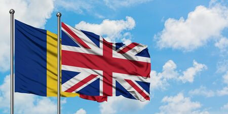 Romania and United Kingdom flag waving in the wind against white cloudy blue sky together. Diplomacy concept, international relations.