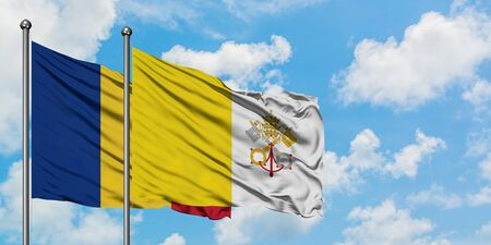 Romania and Vatican City flag waving in the wind against white cloudy blue sky together. Diplomacy concept, international relations.
