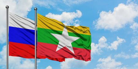 Russia and Myanmar flag waving in the wind against white cloudy blue sky together. Diplomacy concept, international relations.