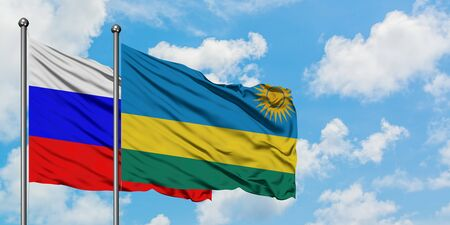 Russia and Rwanda flag waving in the wind against white cloudy blue sky together. Diplomacy concept, international relations. Foto de archivo