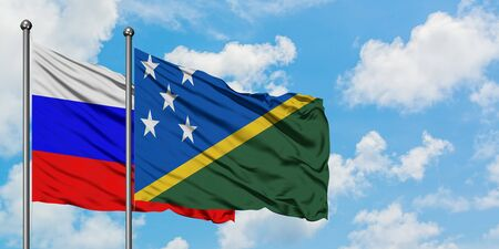 Russia and Solomon Islands flag waving in the wind against white cloudy blue sky together. Diplomacy concept, international relations.